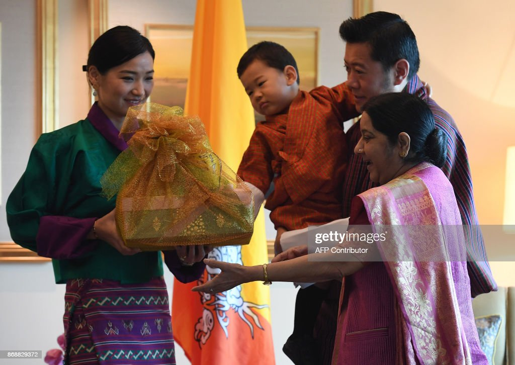 Indian Foreign Minister Sushma Swaraj (R) presents gifts to Bhutans King Jigme Khesar Namgyel Wangchuck (2R) as Queen Jetsun Pema (L) and prince Jigme Namgyel Wangchuck (C) look on prior to a meeting in New Delhi on November 1, 2017. The Bhutanese royal family are in India on a four day visit. /