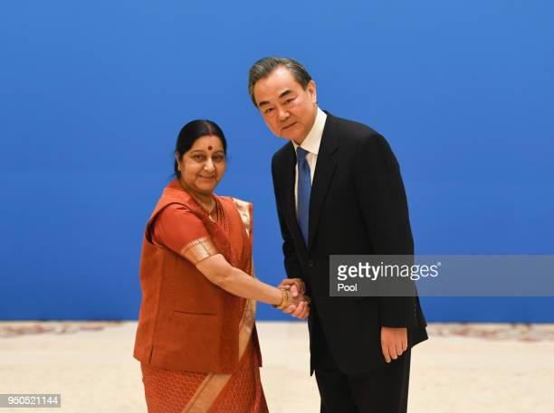 Indian Foreign Minister Sushma Swaraj shakes hands with Chinese State Councilor and Foreign Minister Wang Yi before a meeting of foreign ministers...
