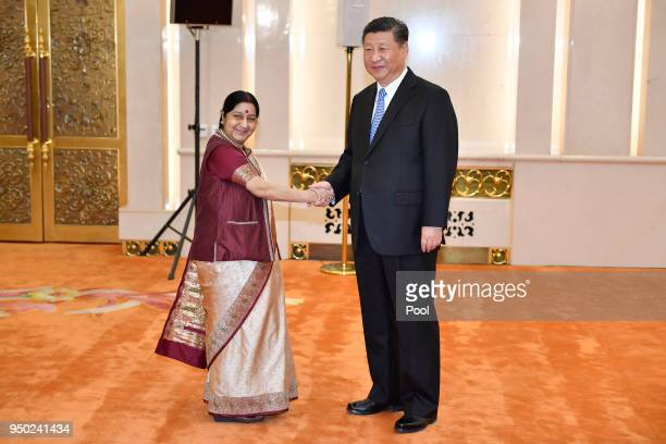 Indian Foreign Minister Sushma Swaraj shakes hands with Chinese President Xi jinping before a meeting at the Great Hall of the People in Beijing...