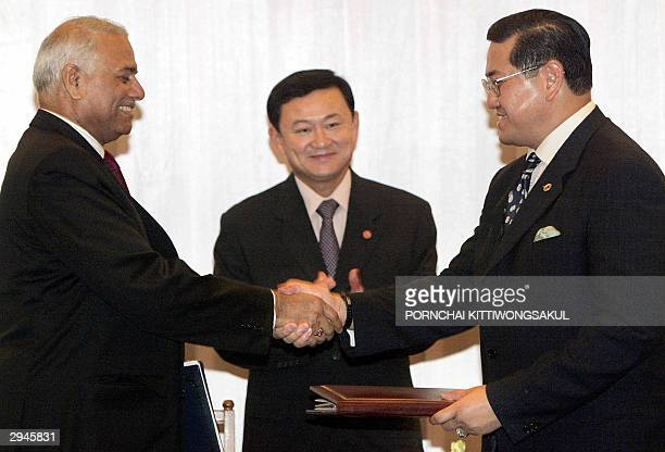 Indian Foreign Minister Yashwant Sinha shakes hands with Thai Foreign Minister Surakiart Sathirathai while exchanging agreements as Thai Prime...