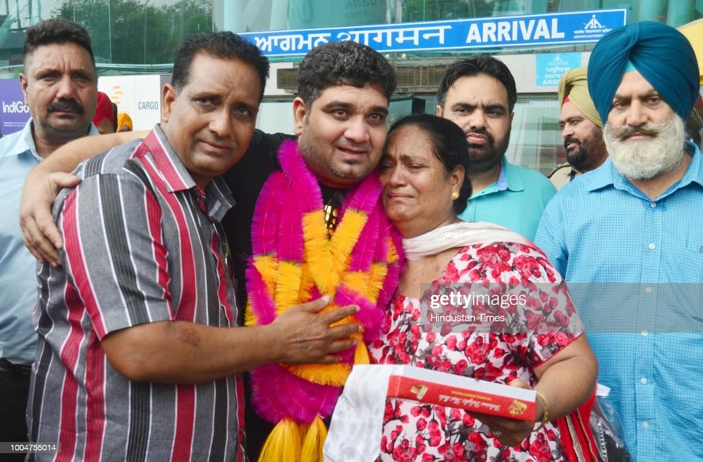 Indian former prisoner Sandeep greets his sister Harjinder Kaur and brother Harjinder Singh as he walks out of the international airport on July 24...