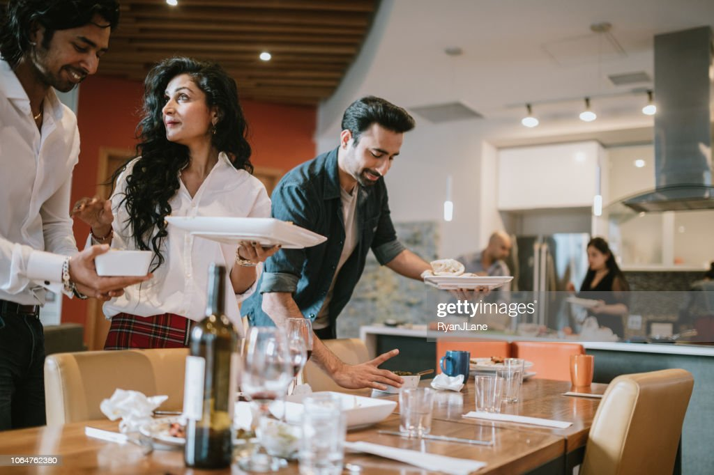 Indian Friends and Family Clean Up After Meal : Stock Photo