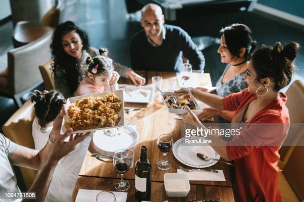 indian friends and family share traditional meal together - rice food staple stock pictures, royalty-free photos & images
