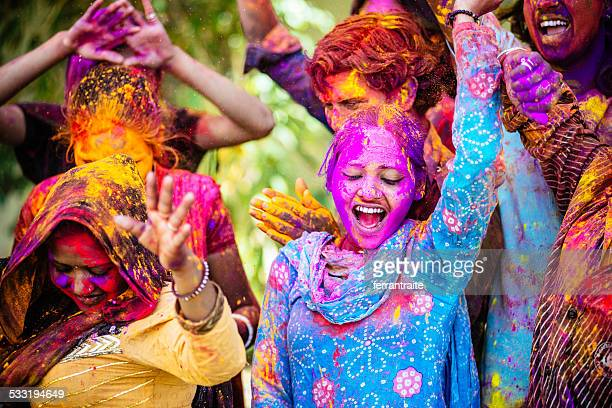 indian friends dancing covered on holi colorful powder in india - culturen stockfoto's en -beelden
