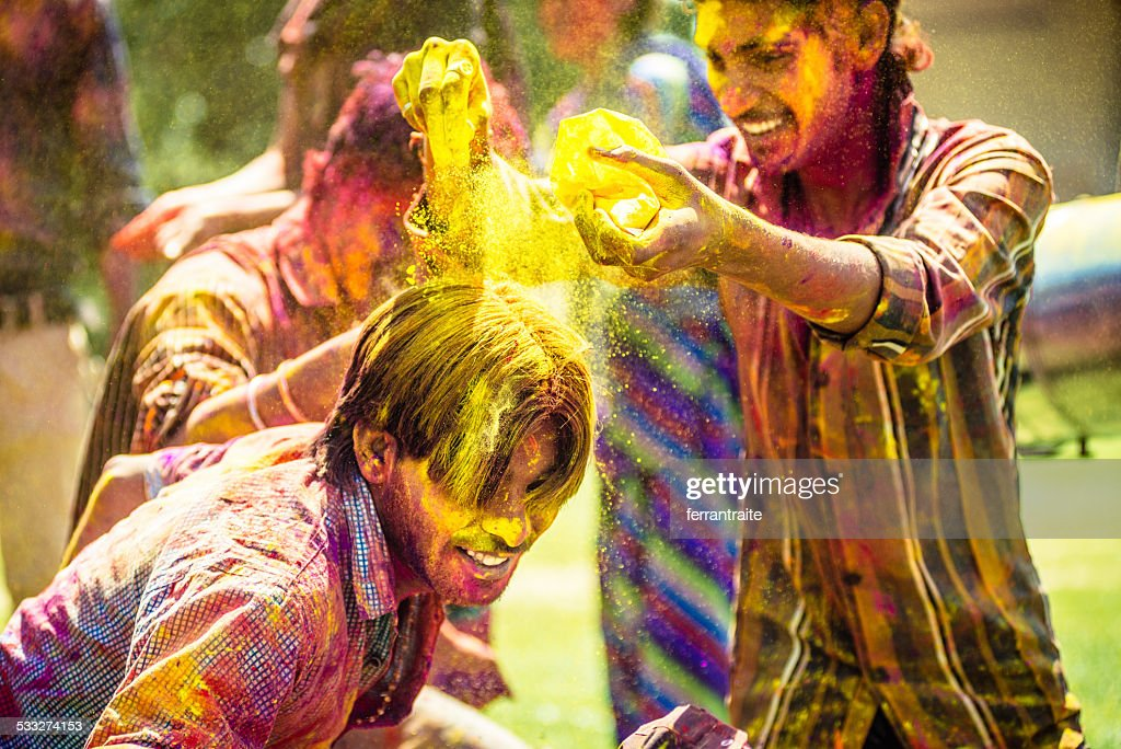 Indian friends throwing Holi Colorful Powder at each other : Stock Photo