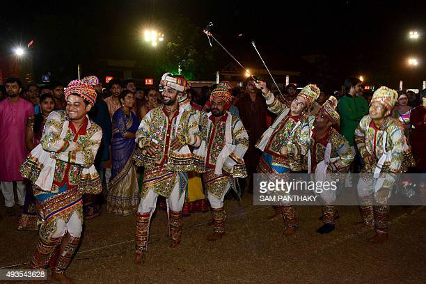 Indian 'garba' performers carry 'selfie sticks' during a dance performance on the 'eighth night of nine nights' termed 'Navratri' at the Rajpath Club...