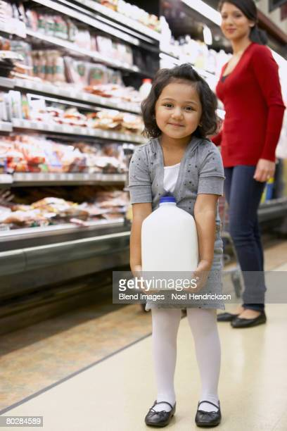 indian girl carrying milk in grocery store - milk carton stock photos and pictures