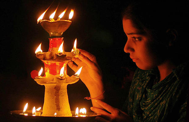 Indian girl Franky lights an earthen lamp in Amritsar in India`s northwestern state of Punjab 31 October 2005 on the eve of the Indian festival of...