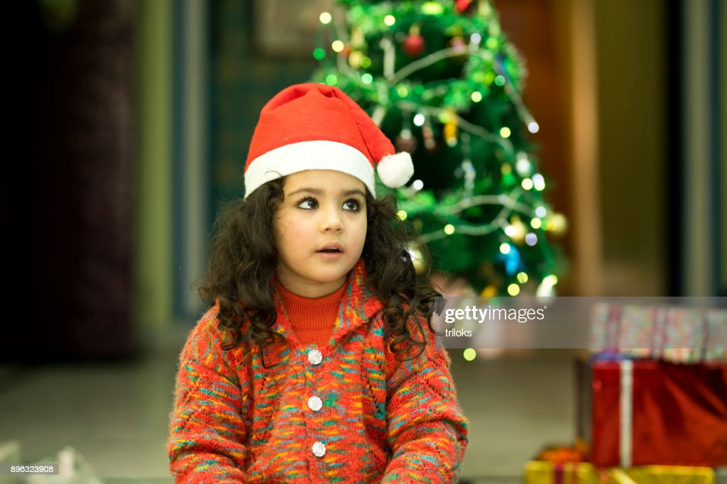 278eb8ed058 ... indian girl in santa hat with christmas gift stock photo