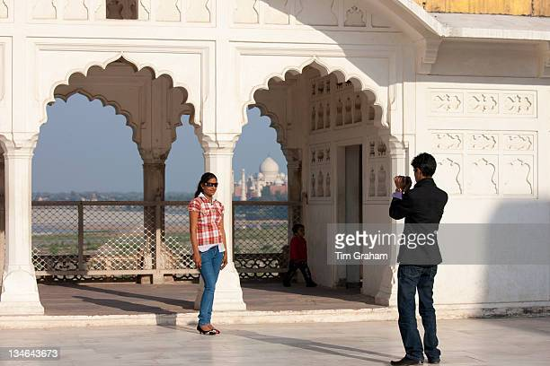 Indian girl in western clothes poses in front of view of Taj Mahal from Khas Mahal Palace at Agra Fort India