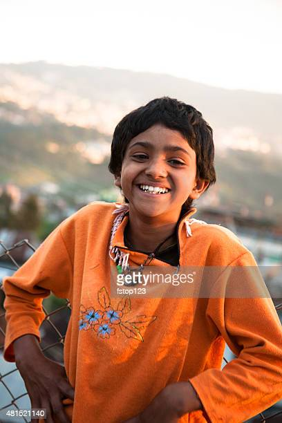 Indian girl on rooftop of building overlooking Shillong, India.