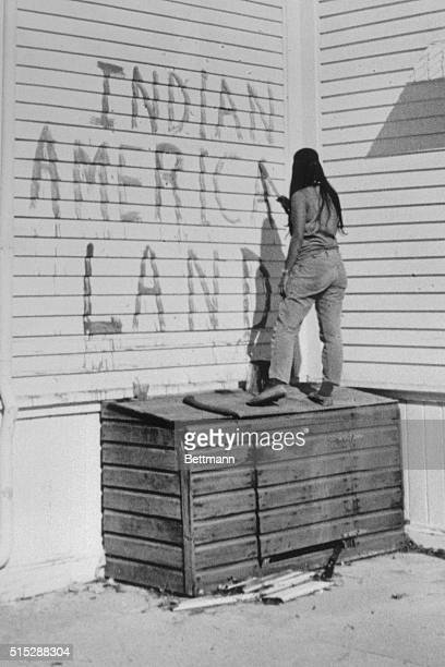 Indian girl one of 78 who invaded Alcataz Island for the second time within two weeks paints sign reading Indian American Land on wall of building at...
