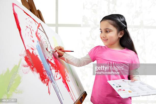 Indian girl painting on canvas in art studio