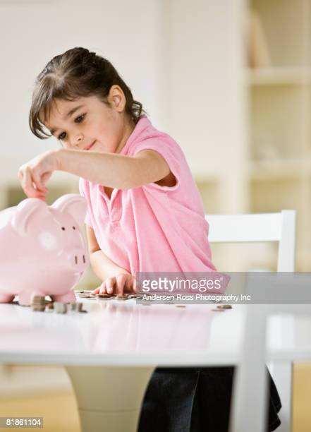 Indian girl putting coins in piggy bank