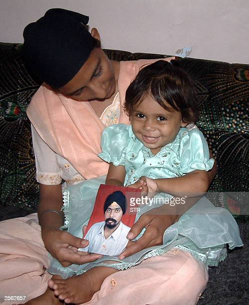Indian girl Shipti Kaur smiles as she sits on her mother Gurjit Kaur's lap holding a photograph of her late father Jasprit Singh in Ahmedabad 23...