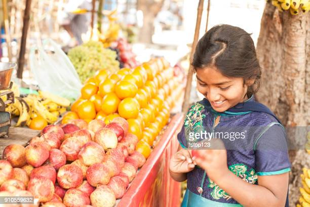 indian girl shops at a local market. - india market stock photos and pictures