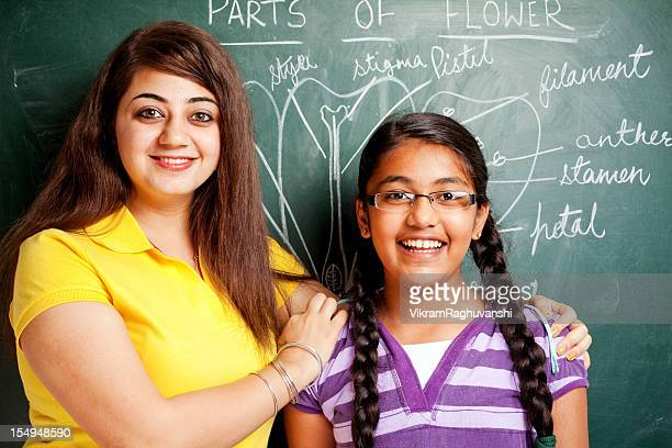 Indian Girl Student Teacher showing Parts of Flowers Chalk Drawing