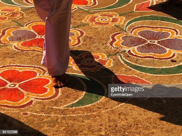 Indian girl walking barefoot in her sari in a temple on colorful drawn Mandalas as flowers on January 06 2008 in Pushkar India