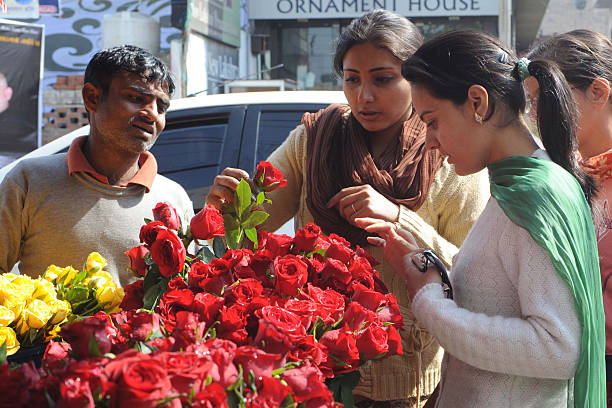 Indian girls buy roses from a vendor on the occasion of Valentine`s day in Amritsar on February 14 2012 Righwing Hindu organisation Shiv Sena...