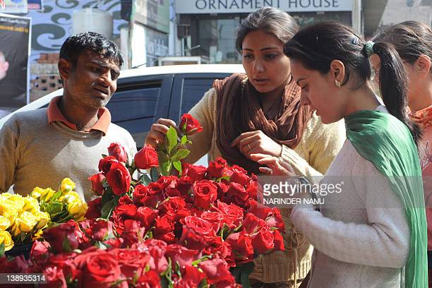 Indian girls buy roses from a vendor on the occasion of Valentine's day in Amritsar on February 14 2012 Righwing Hindu organisation Shiv Sena...