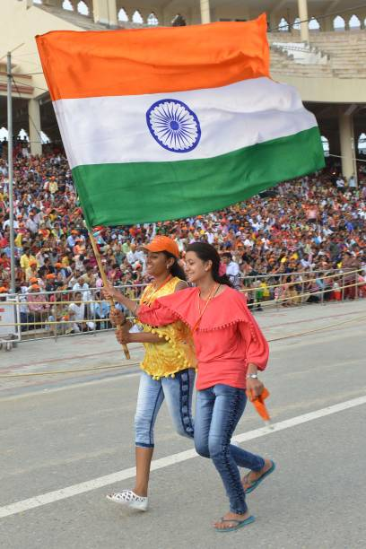 Indian girls carry an Indian flag during the beating retreat ceremony at the India Pakistan Wagah Border post in Amritsar on August 2 2017 / AFP...