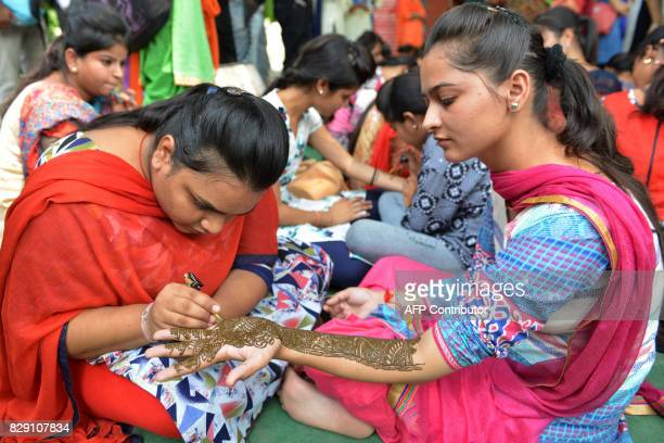 Indian girls decorate each other's hands with henna during the Teej festival to mark the Sawan month at a college in Amritsar on August 10 2017 / AFP...