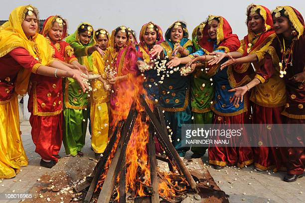 Indian girls dressed as Punjabi dancers gather around a bonfire at the Jagat Jyoti High School in Amritsar January 12 2011 prior to the Lohri...