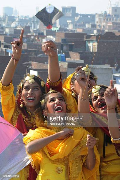 Indian girls dressed as Punjabi folk dancers gesture as they fly kites at a school in Amritsar on January 12 2012 prior to the Lohri festival The...
