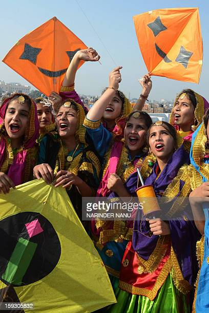 Indian girls dressed as Punjabi folk dancers gesture as they fly kites at a school in Amritsar on January 11 2013 on the eve of Lohri festival The...