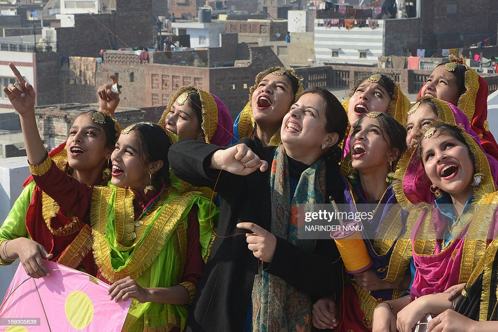 Indian girls dressed as Punjabi folk dancers gesture as they fly kites at a school in Amritsar on January 11, 2013 on the eve of Lohri festival
