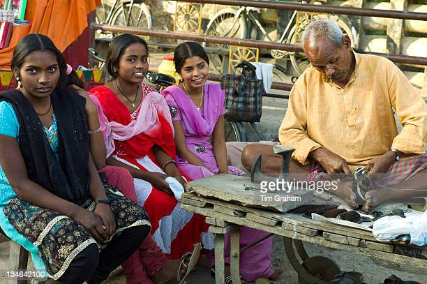 Indian girls in shoe shop with cobbler at work at Sarnath near Varanasi Benares Northern India