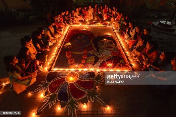 Indian girls light earthen lamps on a Rangoli as they celebrate Diwali the Festival of Lights in Guwahati on November 6 2018 Diwali the Festival of...