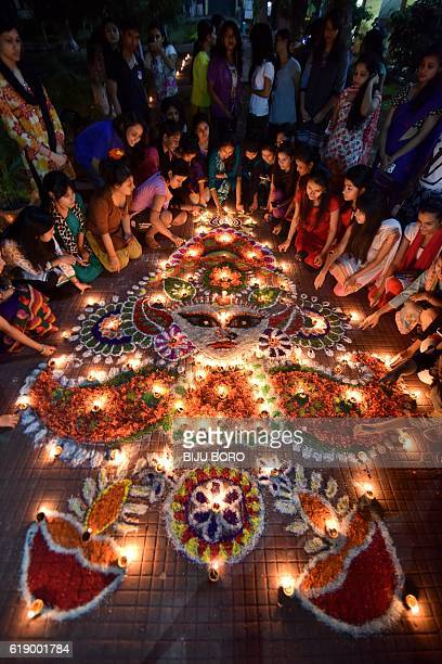 Indian girls light earthen lamps on a rangoli as they celebrate Diwali the Festival of Lights in Guwahati on October 29 2016 The Hindu Festival of...