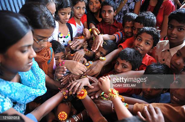 Indian girls tie rakhis or sacred strings to the wrists of young boys at a children's shelter during the Raksha Bandhan festival in Hyderabad on...