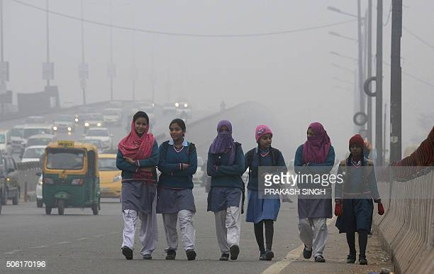 TOPSHOT Indian girls walk to their school on a cold foggy morning in New Delhi on January 22 2016 AFP PHOTO/Prakash SINGH / AFP / PRAKASH SINGH
