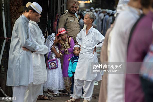 Indian girls whisper as Muslims pray in a side street near the Jama Masjid mosque on the occasion of the Eid alFitr festival which marks the end of...