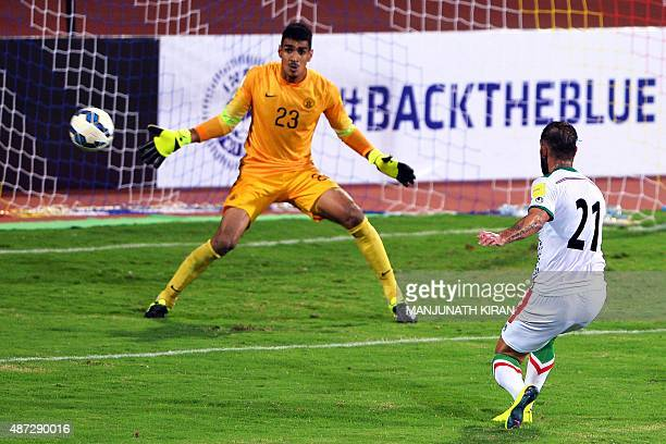 Indian goalkeeper Gurpreet Singh Sandhu looks on while Iranina player Ashkan DeJagah attempts a goal during the Group D FIFA World Cup 2018...