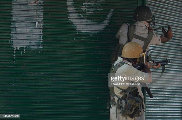 TOPSHOT Indian government forces aim a sling shot and pelletgun towards Kashmiri protestors during a clash in downtown Srinagar on September 25 2016...