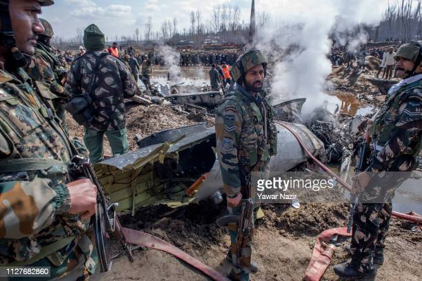 Indian government forces and Indian military forces gather around the debris of crashed Indian Air Force plane on February 27 2019 in Budgam west of...