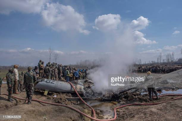 Indian government forces and Indian military forces gather near the debris of crashed Indian Air Force plane on February 27 2019 in Budgam west of...