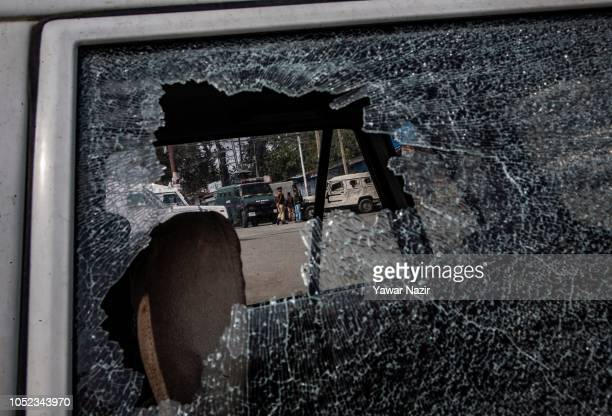 Indian government forces are seen through a broken car shield near the site after a gun battle between Indian government forces and Kashmiri rebels...