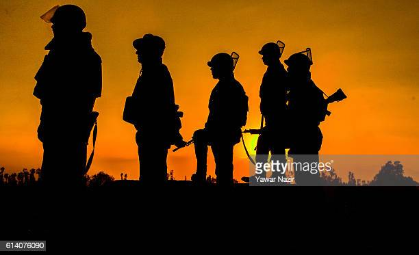 Indian government forces are silhouetted against the setting sun as they look towards the building which is being stormed by Indian government forces...