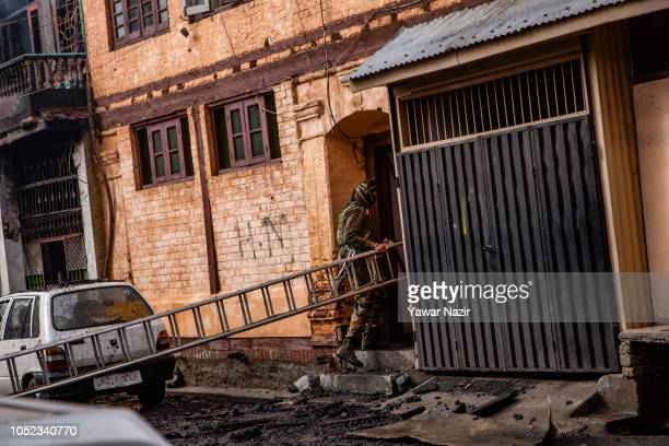 Indian government forces carrying a ladder enter an adjacent house to retrieve the body of their comrade killed in a gun battle between Indian...