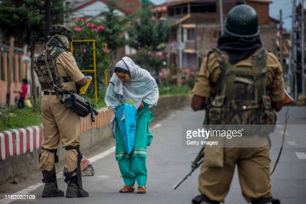 Indian government forces check the prescriptions of a woman before allowing her to walk towards the hospital amid curfew like restrictions in the old...