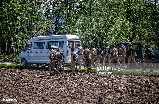 Indian government forces follow an ambulance carrying the bodies of Kashmiri rebels killed in a gun battle between militants and Indian government...