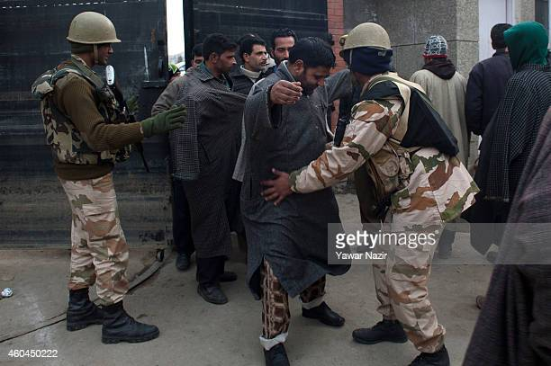 Indian government forces frisk Kashmiri voters before entering the polling station to cast their votes during the fourth phase of assembly elections...