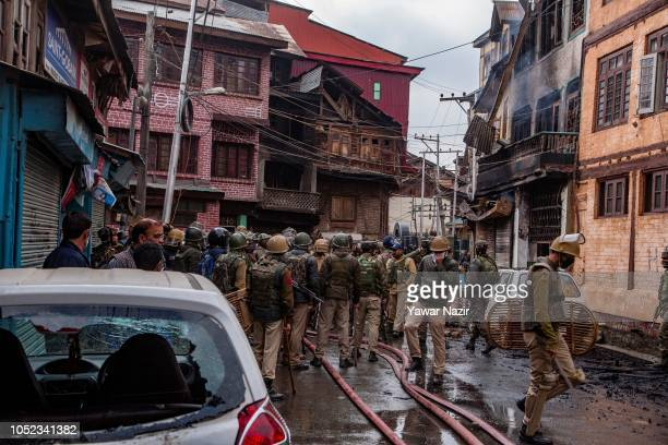 Indian government forces gather on the debris of a ravaged residential house after a gun battle between Indian government forces and Kashmiri rebels...