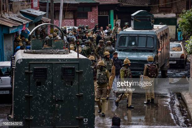 Indian government forces gather outside residential house after a gun battle between Indian government forces and Kashmiri rebels on October 17 2018...