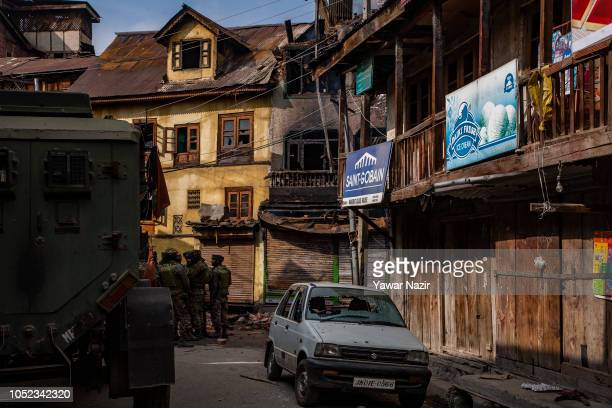 Indian government forces gather outside war ravaged residential house after a gun battle between Indian government forces and Kashmiri rebels on...