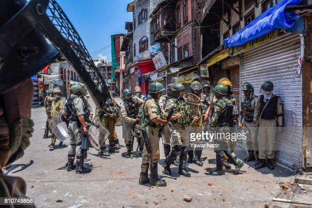 Indian government forces look towards Kashmiri Muslim protesters throwing stones at them during a protest after Kashmiri Muslims defied curfew on the...